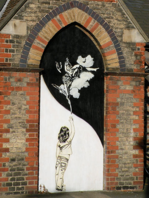 graffiti on a churchside of a child reaching up toward a cloud on which is a small child-angel who is reaching down