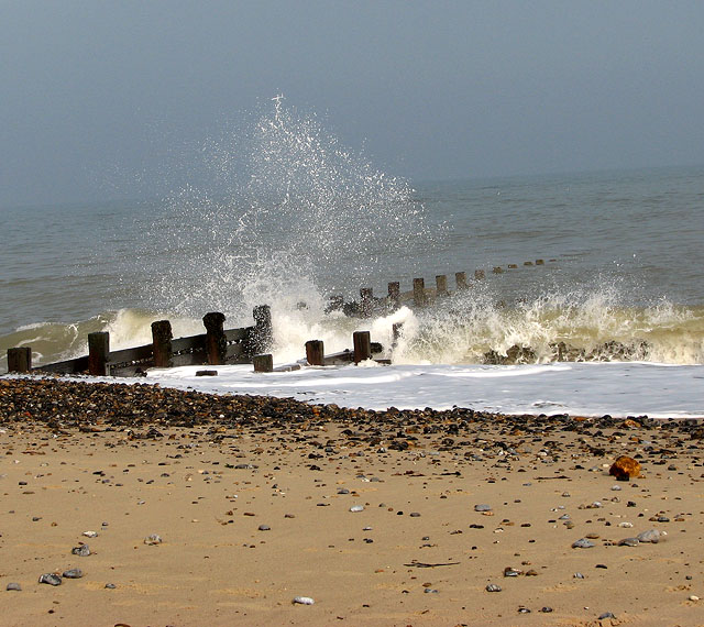 Waves battering wooden groyne