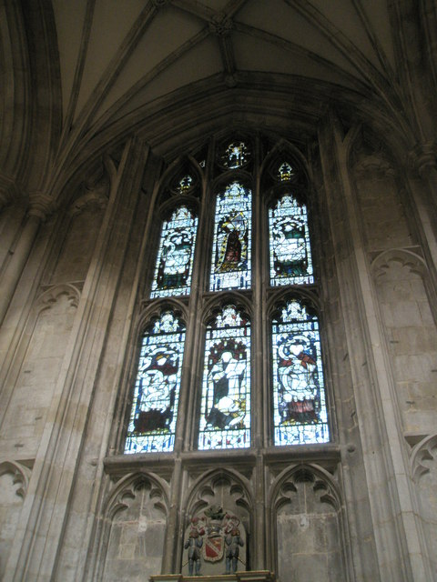 Stained glass window above a coat of arms on the north wall of Winchester Cathedral