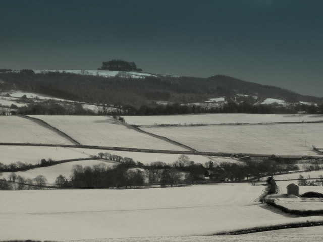 View across snowy fields to May Hill