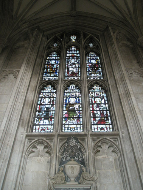 Stained glass window above an urn on the north wall at Winchester Cathedral