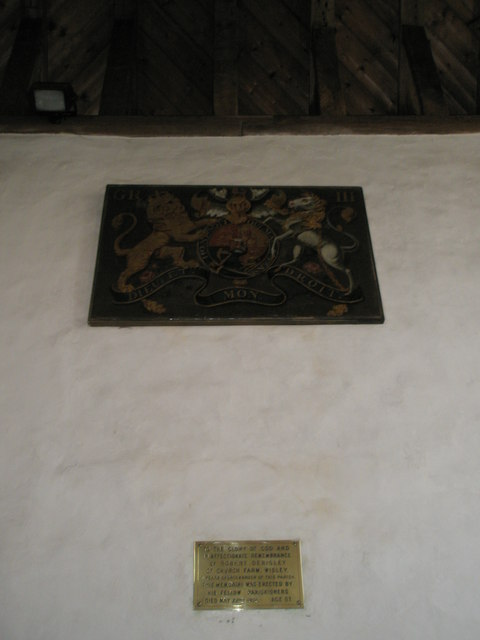 Coat of arms above a brass memorial at Wisley Parish Church