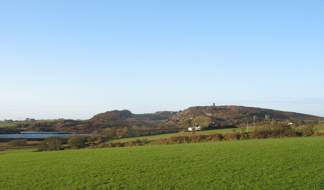 View across grazing land towards pits at the base of Mynydd Parys