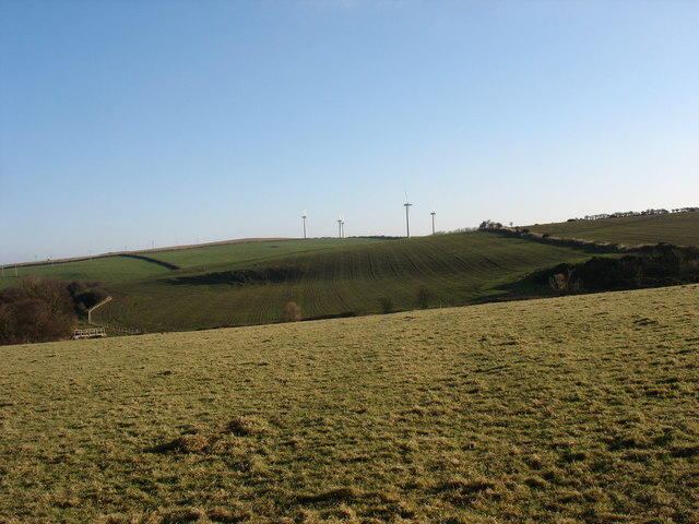 View eastwards across undulating pasture land towards the windfarm