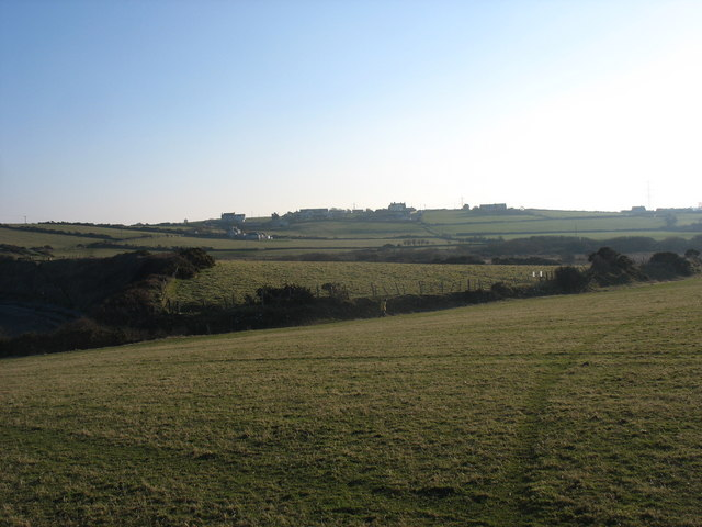 View south across farmland from the cliff top towards houses on the A5025