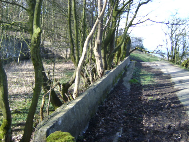 Path along fallen wall of old reservoir