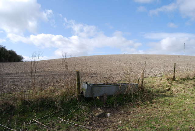 A chalky field behind a water trough