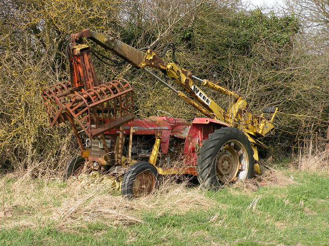 Abandoned Massey Ferguson tractor with Webb grab