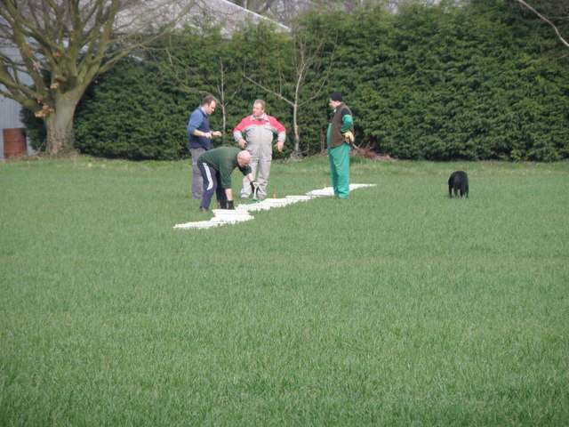 Four men and their dog went to calibrate their spreader