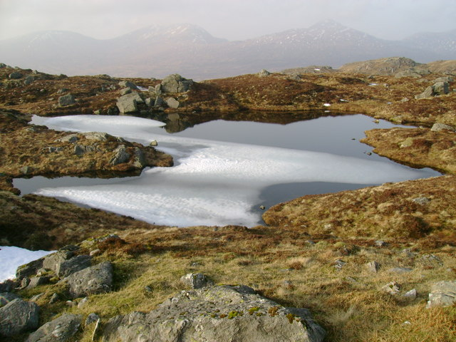 Snow floating on small lochan