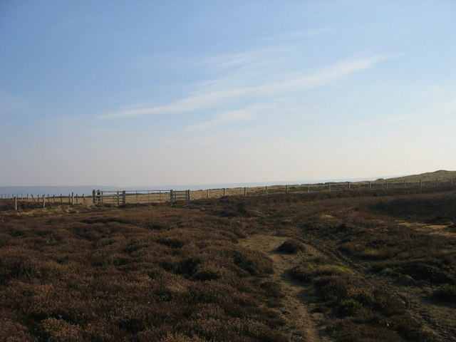 Moorland track leading to blocked gate