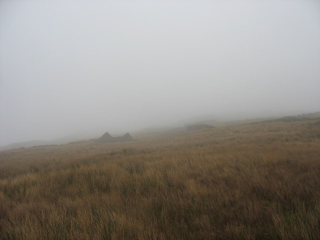 View across a foggy boggy mountainside towards a ruined barn