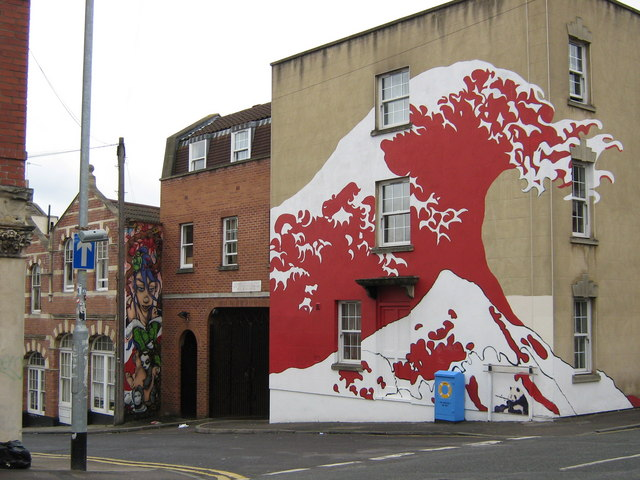 graffit of a tidal wave, painted in red on the side of a building