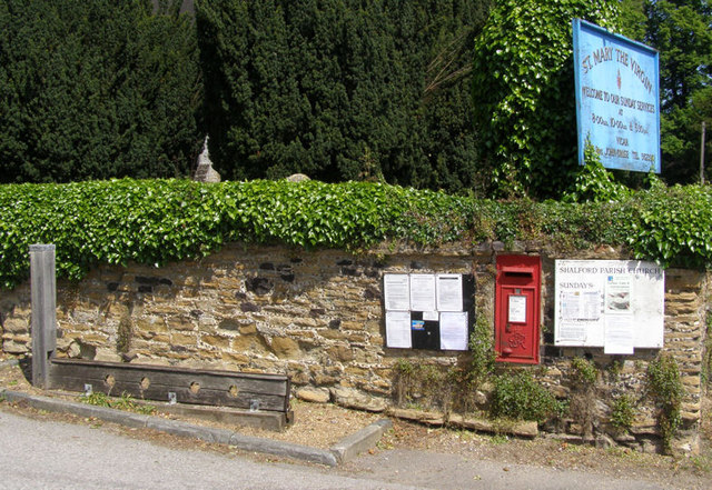 The Village Stocks and wall of St Mary the Virgin Church, Shalford