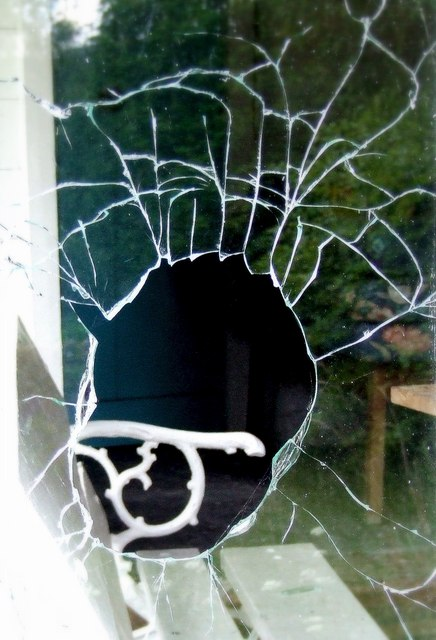 Broken window in a vandalised cottage