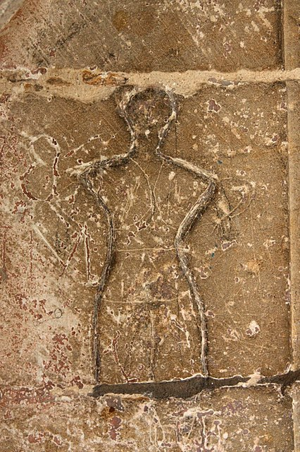 17th/18th century graffiti by the south door of St.Thomas's church, raised clay outline of a human figure