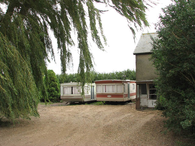 Caravans by derelict farm cottages