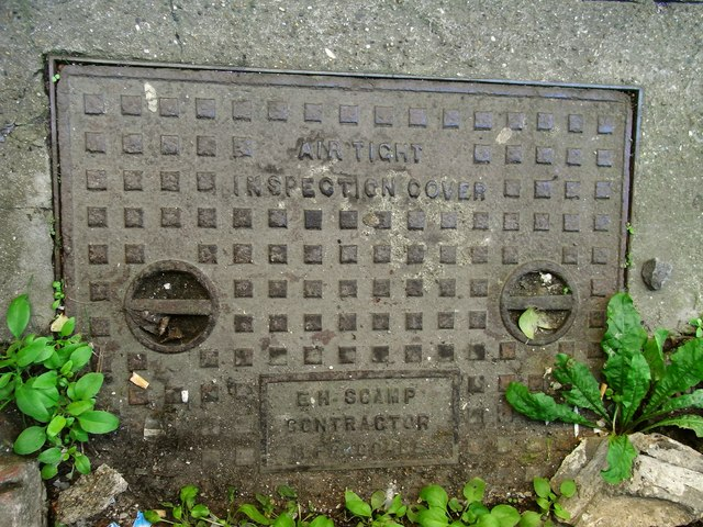 Inspection cover bearing the name E H Scamp, Contractor, Ilfracombe