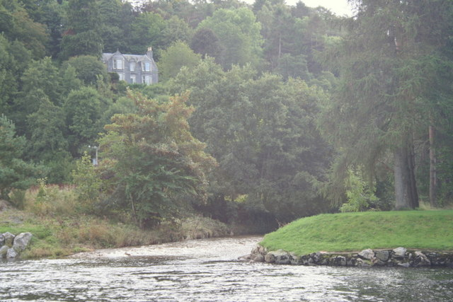 Tree clad house overlooking the river Fiddich