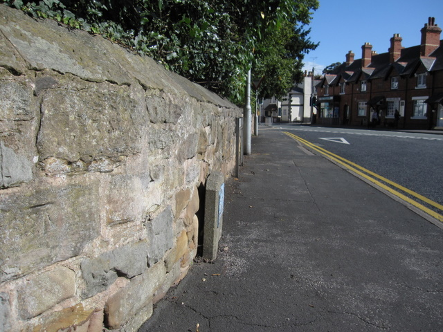 Stone wall and a bench mark in Gladstone Way
