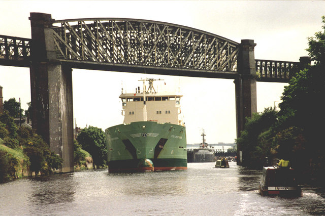 Ship passing narrow boats at the narrowest point on the Manchester Ship Canal