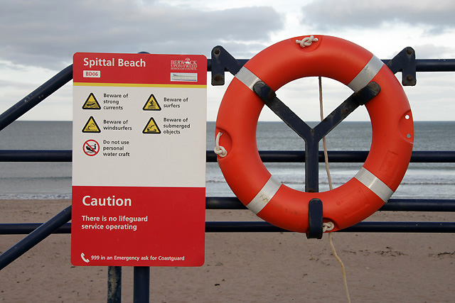 A sign and lifebelt at Spittal Beach