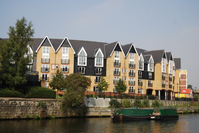 A working narrowboat passes new flats in Maidstone