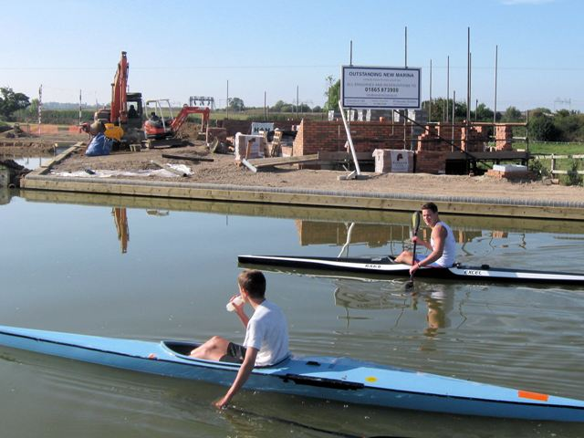 Kayaks pass the site of the marina facilities block