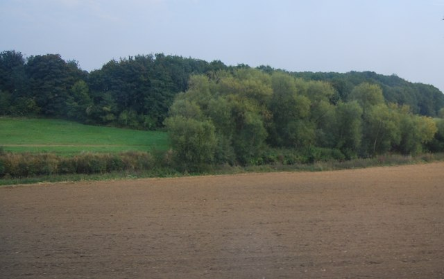 Tree lined River Medway behind a ploughed field