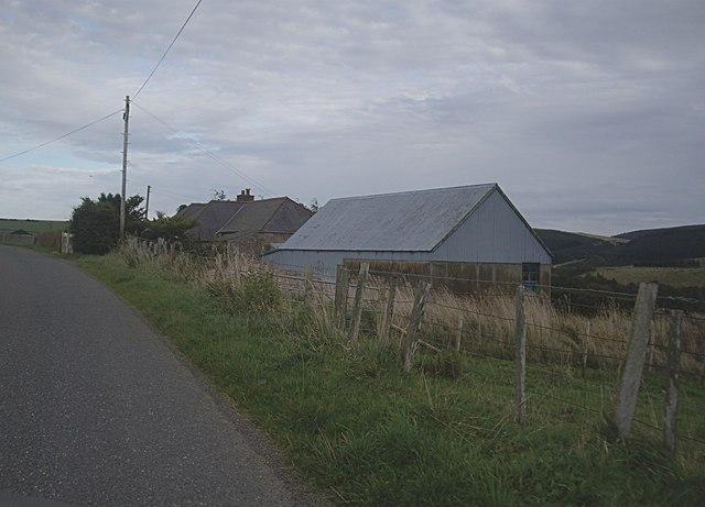 Barn by roadside cottages