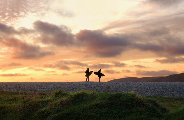Surfers silhouetted at sunset, Newgale