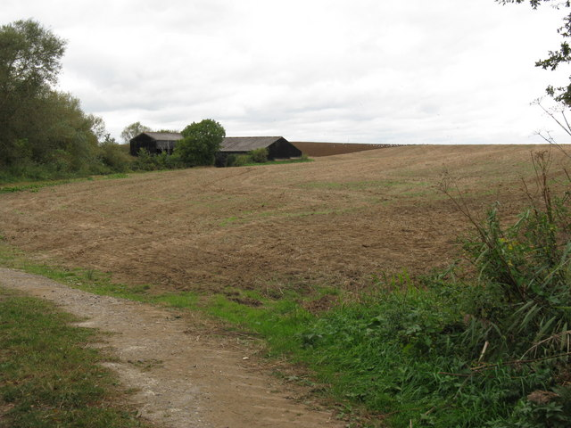 Part ploughed field next to black farm buildings