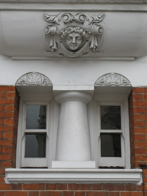Smirking face above a window in Treborough House, Nottingham Place / Paddington Street, W1