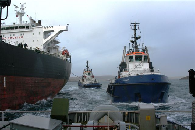 Tanker Overseas Shirley being escorted into Sullom Voe oil terminal by tugs