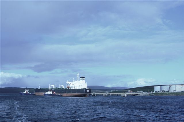 Tanker alongside jetty one with two tugs pushing on while mooring ropes are being run