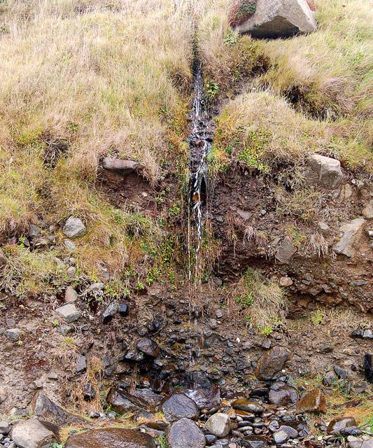 Small waterfall trickling onto Porthmelgan beach