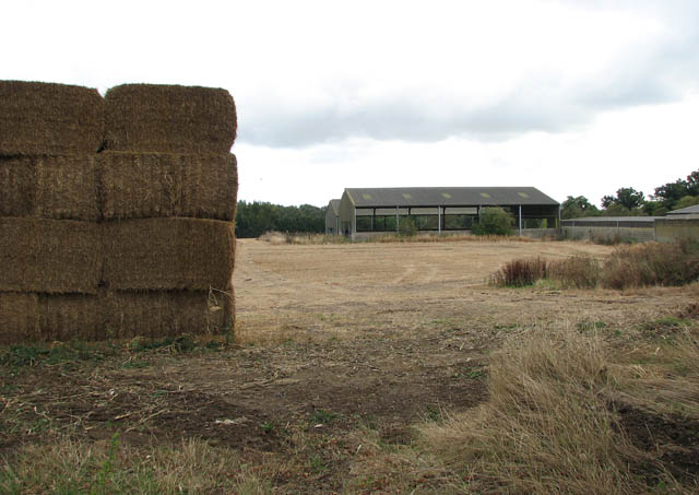 Sheds and stacked bales at Brundall Barn Farm