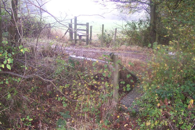 Footbridge, stile and farm track near Bowzell Wood