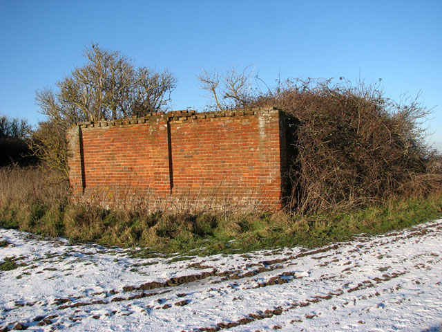 Remains of a brick barn beside the path to Hales Hall