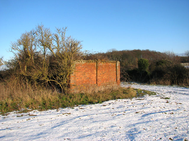 Remains of a brick barn in the corner of a field