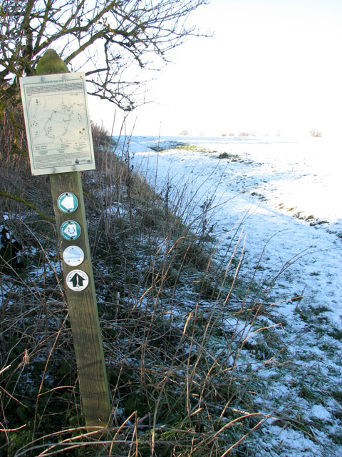 Footpath marker and map beside derelict farm buildings