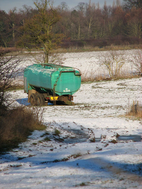 Farm trailer parked in snowy field west of Hales Hall