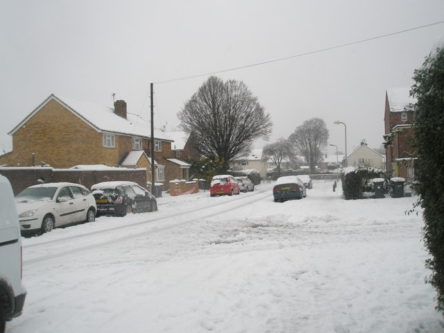 Approaching the junction of  a snowy Hazleholt Drive and Burgate Close