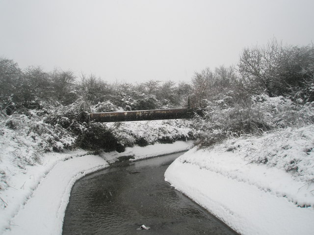 Pipe crossing a snowy Hermitage stream