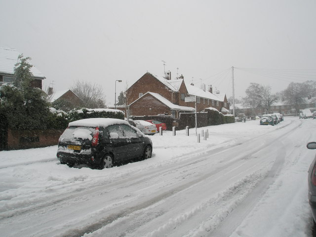 Approaching the junction of  a snowy Woodgreen Avenue and Timsbury Crescent
