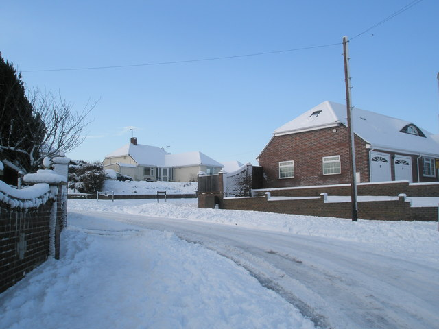 Approaching the junction of  a snowy Littlepark Avenue and Ashwood Close