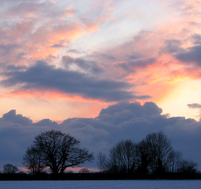 Fiery sunset and snow clouds over frozen fields