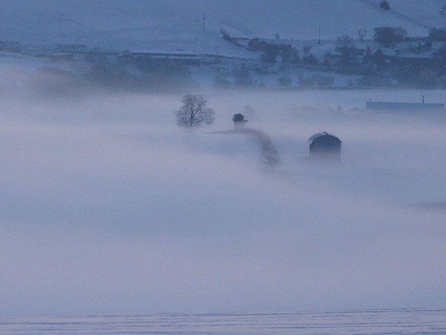 Morning mist over snow-covered fields
