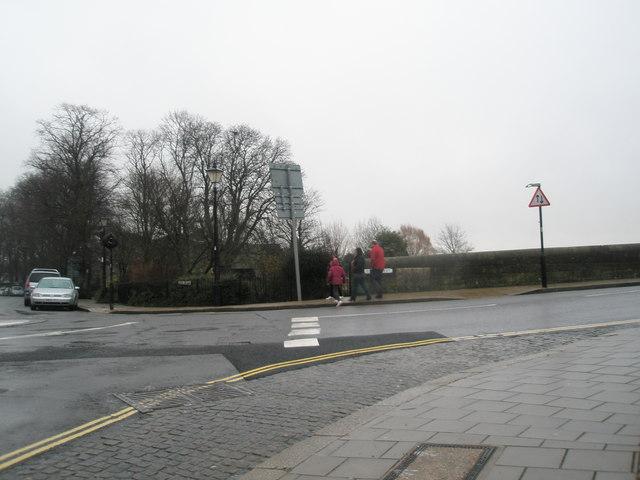 Bedraggled pedestrians leaving the bridge at Queen Street