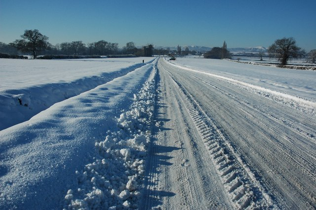 Snow covered road over Dunstall Common